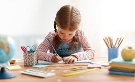 在家读滑稽的儿童的女孩做家庭作业文字和 免版税库存图片