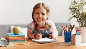 在家读滑稽的儿童的女孩做家庭作业文字和 免版税图库摄影