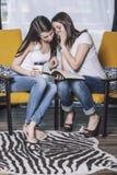 在家谈两个美丽的妇女的朋友愉快的微笑 免版税库存照片