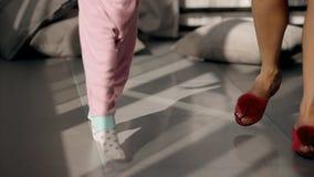 在家走在晴朗的地板上的妇女和女孩的亭亭玉立的腿 股票录像