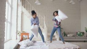 在家跳跃在床和战斗枕头的混合的族种年轻俏丽的女孩获得乐趣 股票视频