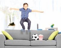 在家跳跃在长沙发的极度高兴的男孩 图库摄影