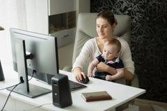 在家运作办公室和照顾她的母亲画象 图库摄影
