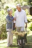在家运作在庭院里的资深夫妇 库存照片