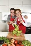 在家运作围裙混合的菜沙拉微笑的美好的美国夫妇厨房愉快 免版税库存照片