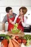 在家运作围裙混合的菜沙拉微笑的美好的美国夫妇厨房愉快 免版税库存图片