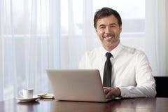 在家远程协作的商人 在膝上型计算机上 微笑 库存图片