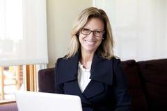 在家远程协作的女实业家 在膝上型计算机上 微笑 免版税库存图片