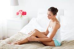 在家适用于奶油的美丽的妇女她的腿 免版税库存图片