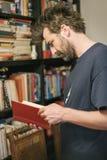 在家选择书的好奇人在他的图书馆里 库存图片
