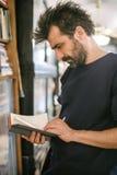 在家选择书的好奇人在他的图书馆里 免版税库存照片