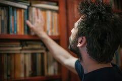 在家选择书的好奇人在他的图书馆里 免版税图库摄影