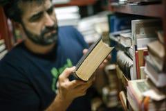 在家选择书的好奇人在他的图书馆里 图库摄影