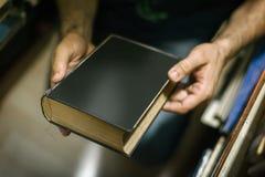 在家选择书的好奇人在他的图书馆里 库存照片