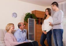 在家遇见他们的儿子的女朋友的父母everning的 免版税库存图片