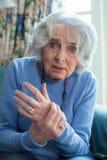 在家遭受与关节炎的资深妇女 免版税图库摄影