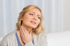 在家遭受喉头痛苦的不快乐的妇女 免版税库存照片
