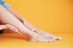 在家遭受在腿的痛苦的年轻亚裔女孩 免版税库存照片