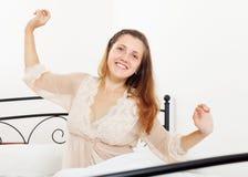 在家醒的nightrobe的快乐的妇女 免版税图库摄影