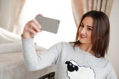 在家采取与她巧妙的电话的一个美丽的浅黑肤色的男人的画象一selfie 免版税库存照片