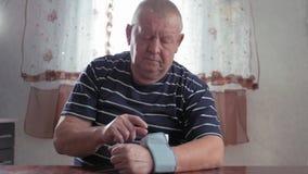 在家采取他的血压在桌上的老人 人健康检查血压 并且与数字心率 影视素材