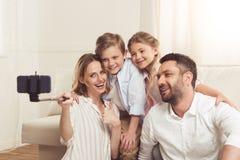 在家采取在智能手机的家庭selfie有monopod的 免版税库存图片