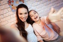 在家采取在电话的母亲和女儿selfie在晚上 免版税库存图片