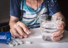 在家采取每日疗程药量的上了年纪的人 库存图片