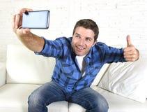 在家采取selfie图片或自已录影有手机的年轻可爱的30s人坐长沙发微笑愉快 免版税库存照片