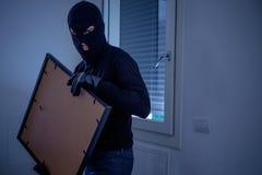 在家里面的窃贼窃取从墙壁的一张绘画 免版税库存图片