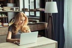 在家键入在膝上型计算机办公室工作场所的微笑的妇女 免版税库存照片