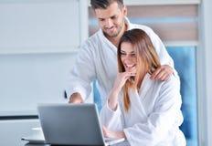 在家食用咖啡在厨房和研究便携式计算机的浴巾的年轻夫妇 库存照片