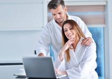 在家食用咖啡在厨房和研究便携式计算机的浴巾的年轻夫妇 免版税库存图片