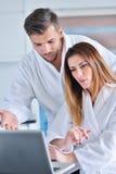 在家食用咖啡在厨房和研究便携式计算机的浴巾的年轻夫妇 免版税库存照片