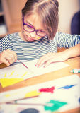 在家绘一个小青春期前的学生的女孩的画象 被定调子的照片 免版税图库摄影