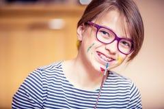 在家绘一个小青春期前的学生的女孩的画象 被定调子的照片 图库摄影