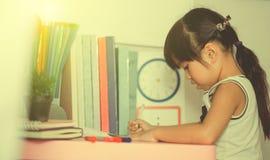 在家读一本书与葡萄酒颜色作用的年轻学校女孩 免版税库存照片