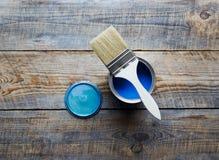 在家绘与在木背景的罐头蓝色油漆 免版税图库摄影