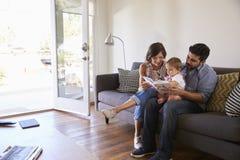 在家读与小女儿的父母在沙发 免版税图库摄影