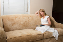 在家读书的妇女在长沙发 免版税库存图片