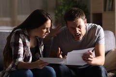 在家读信的愤怒的夫妇 免版税库存图片
