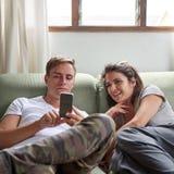 在家结合在有一个手机的长沙发 免版税图库摄影