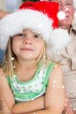在家戴圣诞老人帽子的女孩的综合图象 免版税库存照片