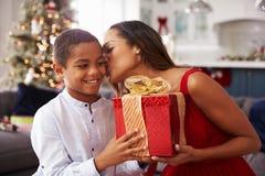 在家给圣诞节礼物的母亲儿子 免版税库存照片