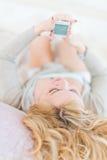 在家读在她明亮的bedro的轻松的妇女一个正文消息 免版税图库摄影