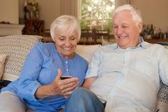 在家读正文消息的愉快的前辈在他们的长沙发 图库摄影