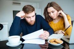在家读他们的票据的夫妇 免版税库存照片
