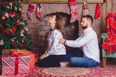 在家给他的妻子后面按摩的丈夫 免版税库存图片