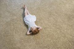在家说谎在地毯的小女孩 免版税图库摄影