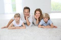 在家说谎在地毯的愉快的家庭 免版税库存照片